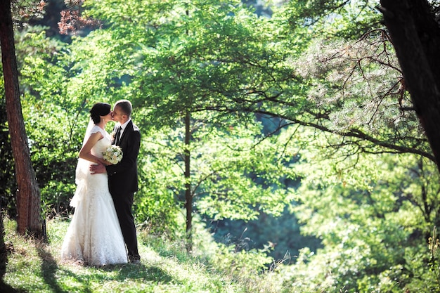 Newlyweds kissing in the forest