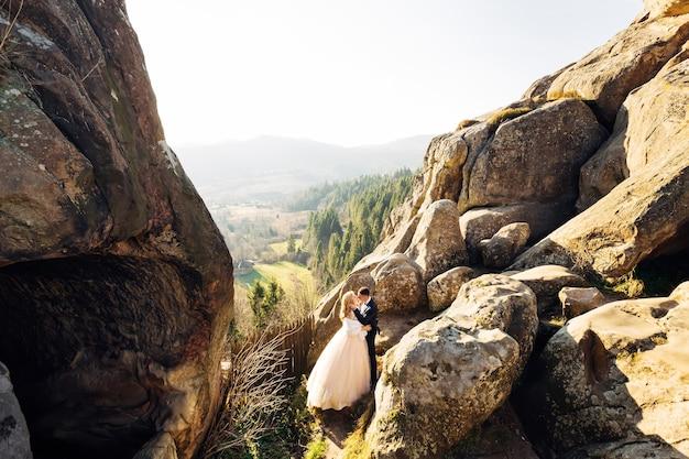 山を見下ろす崖の上でキスする新婚夫婦コンセプトファミリーが結婚したばかり