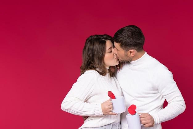 Молодожены целуются на красном фоне, держа белые чашки с сердечками ручной работы.