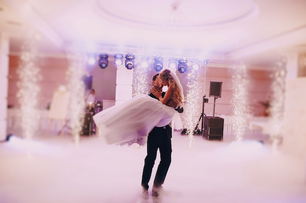 Newlyweds kissing passionately while dancing