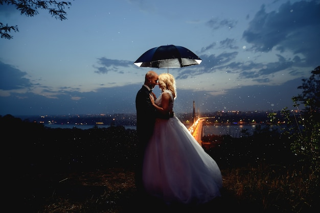 Newlyweds kissing under an umbrella at dusk