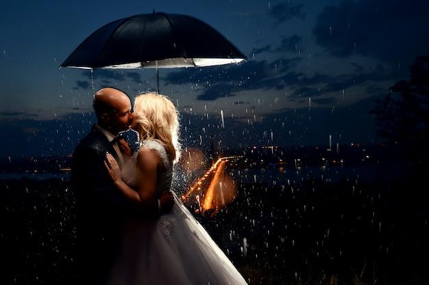 Молодожены целуются под дождем