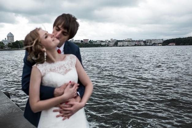 Newlyweds kissing with beautiful landscape background
