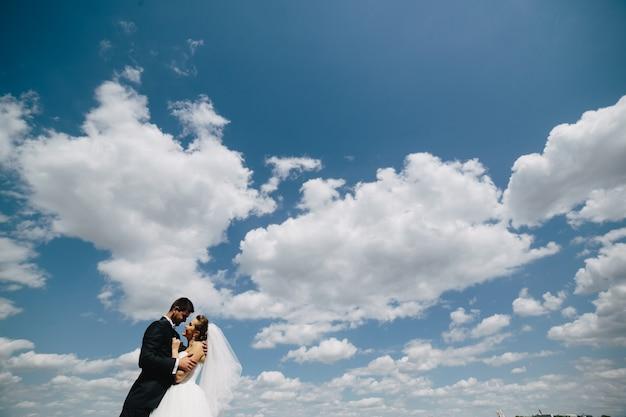 空の背景でお互いを見て新婚夫婦
