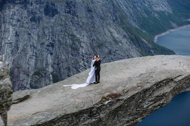 トロールの舌と呼ばれるノルウェーの岩片に新婚夫婦