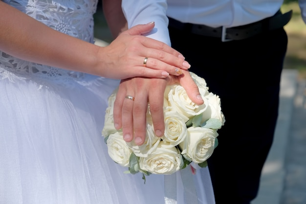 The newlyweds put hands on bouquet. closeup view