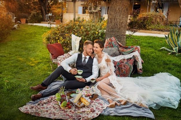 신혼 부부는 일몰에 정원에서 앉아서 차를 마신다.