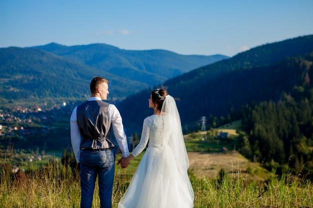 新婚夫婦は山の頂上の牧草地の中で微笑み、抱き合っています。
