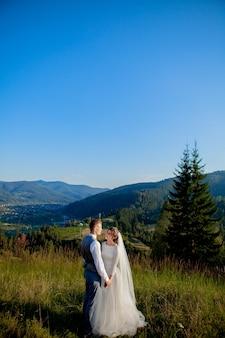 Молодожены улыбаются и обнимаются на лугу на вершине горы.