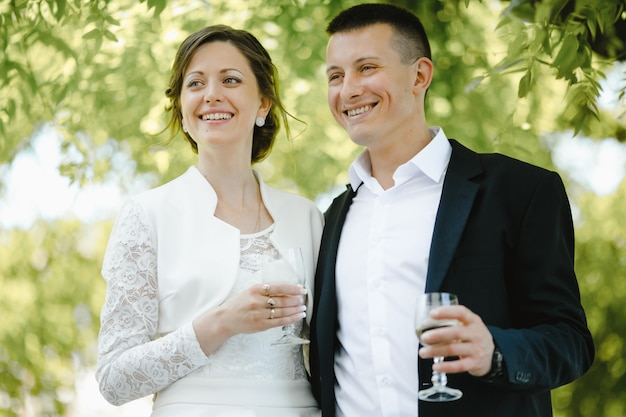 Newlyweds smile and keep glasses with champagne