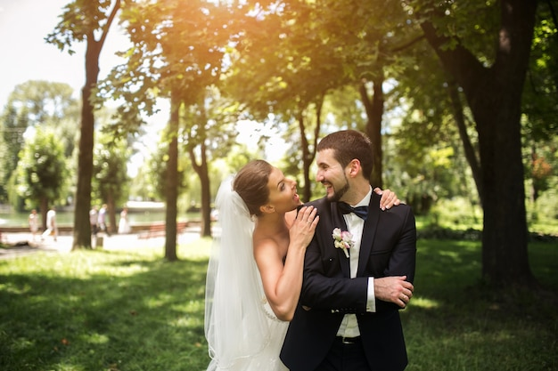 Newlyweds smiling in the park
