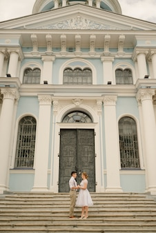 Newlyweds stand against the church with ancient architecture. wedding day.