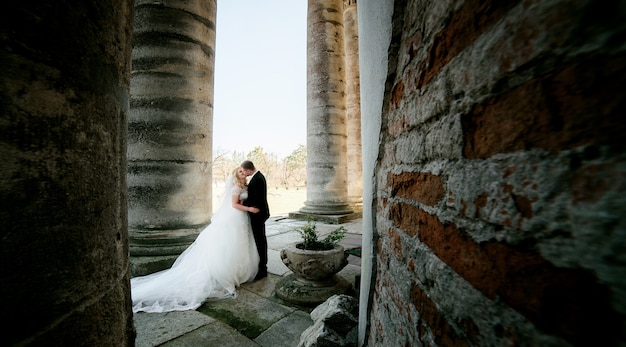 Newlyweds stand between the columns in the evening lights