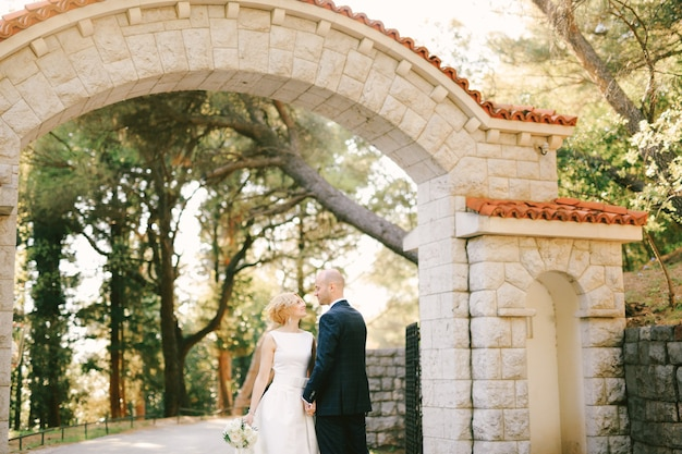 Newlyweds stand in front of a stone gate with orange tiles in a green park holding hands