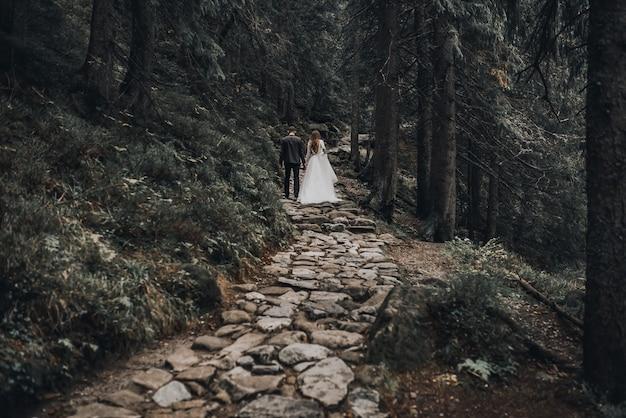 신혼 부부는 어두운 울창한 숲 한가운데 서