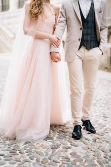 新婚夫婦は、ベルガモイタリアの古い建物に対して敷石の上に立っています