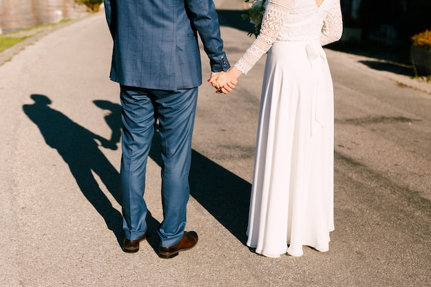 Молодожены стоят на дороге, держась за руки, солнце ярко светит им за спину силуэты невесты и