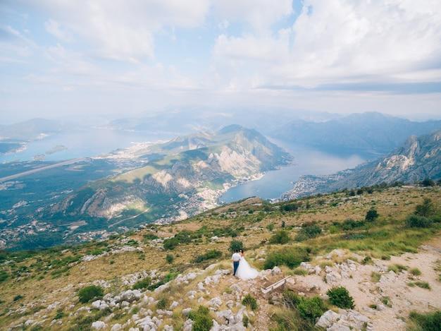 Lovcen 산에 서서 전망을 감상하는 신혼 부부