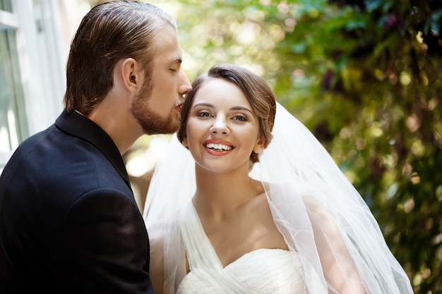 Newlyweds in suit and wedding dress smiling, kissing in park.