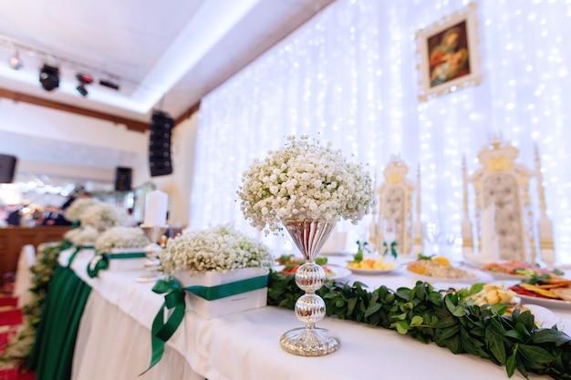 레스토랑 홀에서 꽃 요리와 함께 신혼 테이블 은방울꽃 결혼식