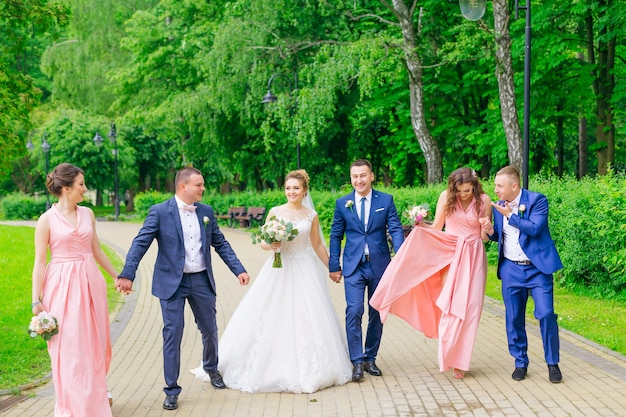 Newlyweds and their friends hold hands and walk in the park.