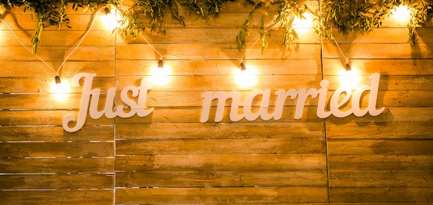 Newlyweds. vintage suspended lights. wooden texture. wedding accessories. the word just married