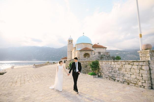 신혼 부부는 고스파 오드 스크르펠라(gospa od skrpela) 섬에 있는 성모 교회의 돌 울타리를 따라 손을 잡고 걷습니다. 고품질 사진