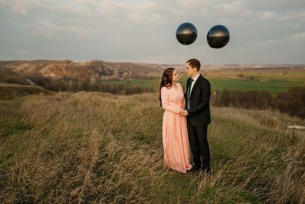 Молодожены гуляют на природе с большими гелиевыми шариками. свадебная концепция