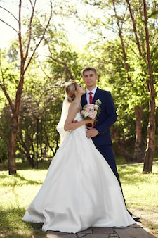 Newlyweds walk in nature in the park after the wedding ceremony