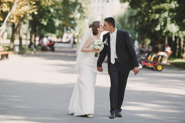 Newlyweds walking and kissing