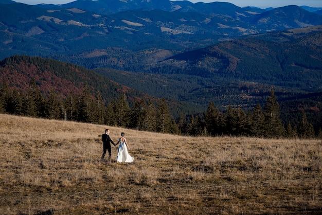 Newlyweds walking through a dry field