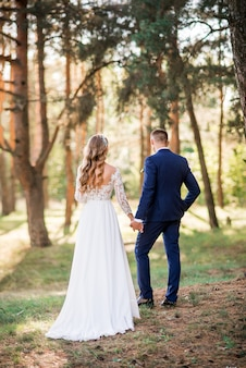 Newlyweds walking together in nature, romantic landscapes for two during a wedding photo shoot.