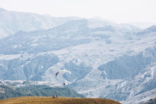 Новобрачные смотрят парашют в небе над грузинскими горами