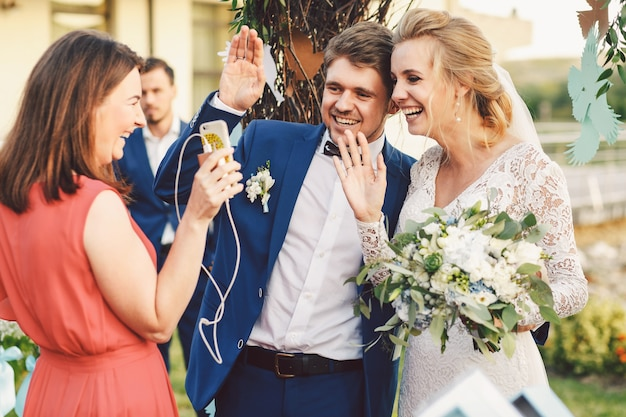 Newlyweds wave with their hands to someone on the phone