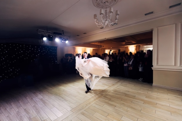 Newlyweds whirl in wedding dance groom hold the bride in his arms
