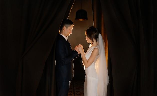 Молодожены с закрытыми глазами держатся за руки. свадьба, любовь, концепция отношений. низкий ключ.