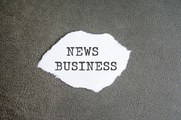 News business sign on the torn paper on the grey background.