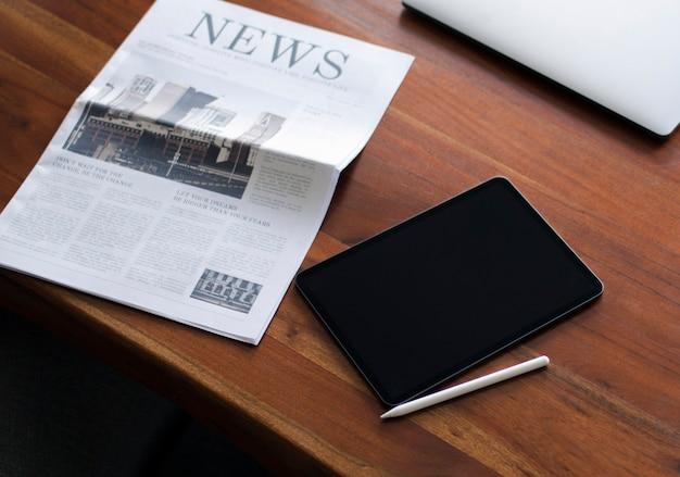 デジタルタブレットとテーブルの上の新聞