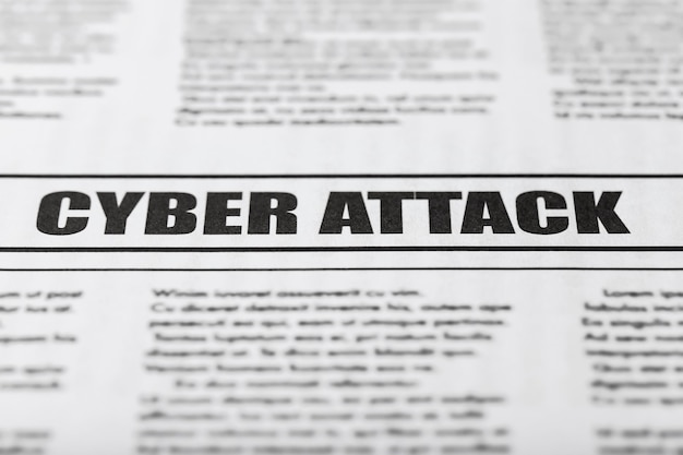 Newspaper with text cyber attack, close up