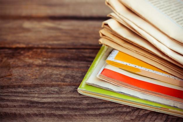 Газеты и журналы на старом деревянном фоне. тонированное изображение. Premium Фотографии