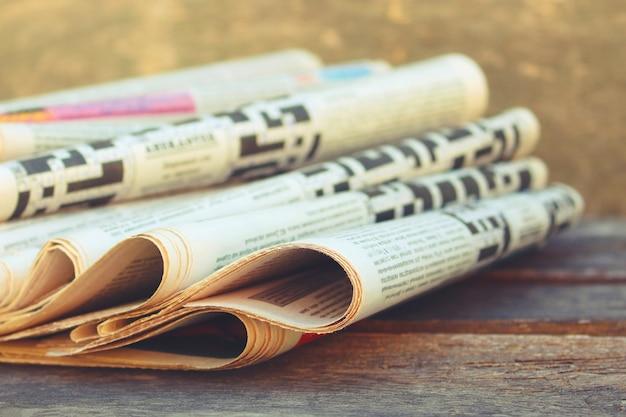 古い木の背景の新聞や雑誌。トーンの画像。