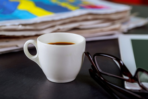 Newspapers and coffee cup, reading glasses and notepad