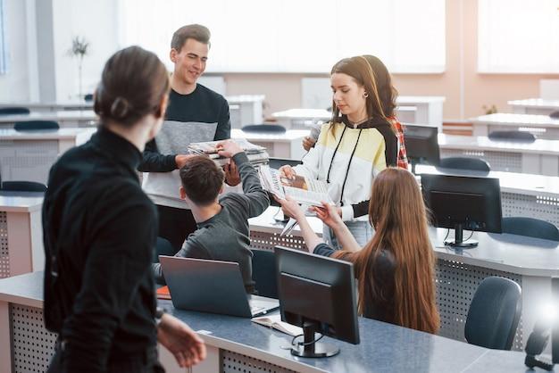 손에 신문. 현대 사무실에서 일하는 캐주얼 옷에 젊은 사람들의 그룹
