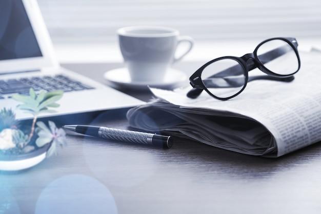 眼鏡とノートパソコン付きの新聞。オンラインニュース。