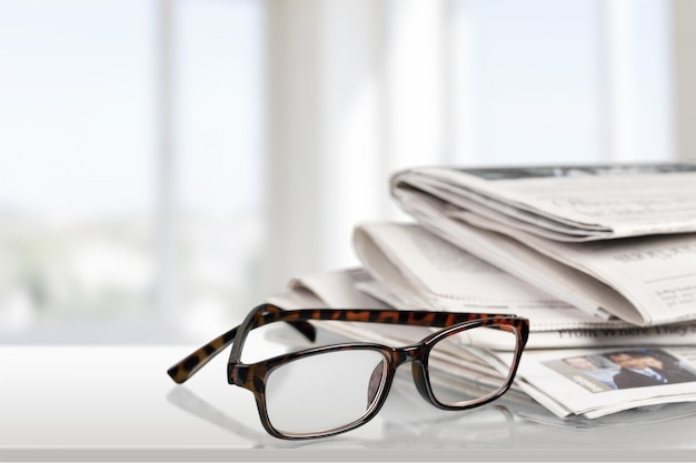 Newspapers with reading glasses on background