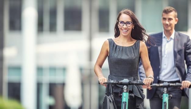 次世代の通勤者は、女性と男性のビジネスパーソンが電動スクーターを使って通勤しています。