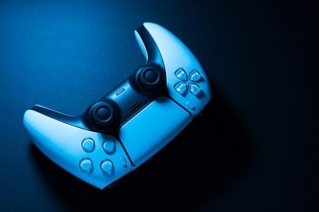검정색 배경에 격리된 차세대 흰색 게임 컨트롤러는 색 조명을 비추고 있습니다. 확대. 선택적 초점입니다.