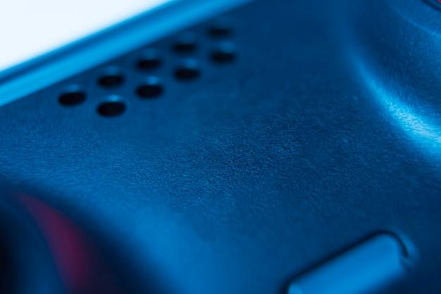 赤と青のライトで黒の背景に分離された次世代の白いビデオゲームコントローラー。マクロをクローズアップ。セレクティブフォーカス。