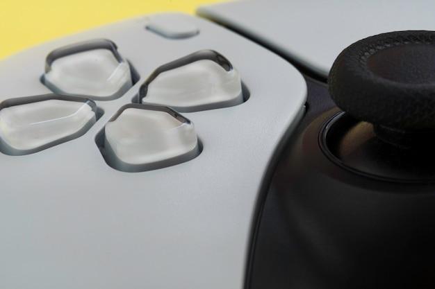 노란색 배경에 격리된 차세대 흰색 비디오 게임 컨트롤러입니다. 매크로 클로즈업입니다. 선택적 초점입니다.