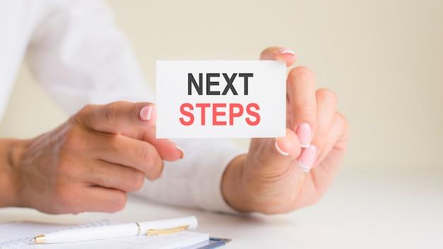 女性の手にある「次のステップ」カード。ビジネス、倫理、広告、マーケティング。